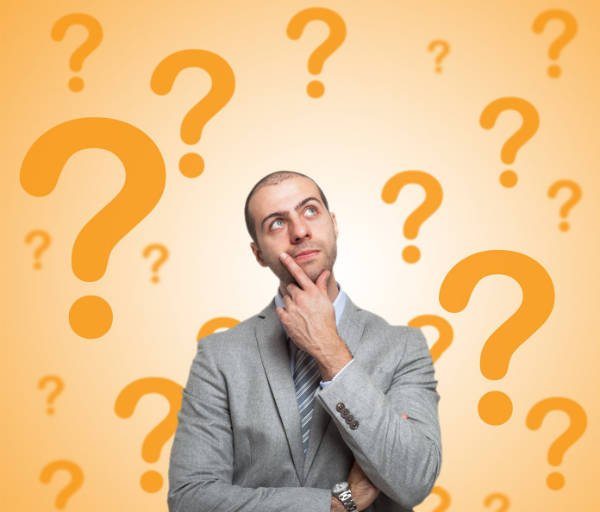 Man surrounded by question marks thinking