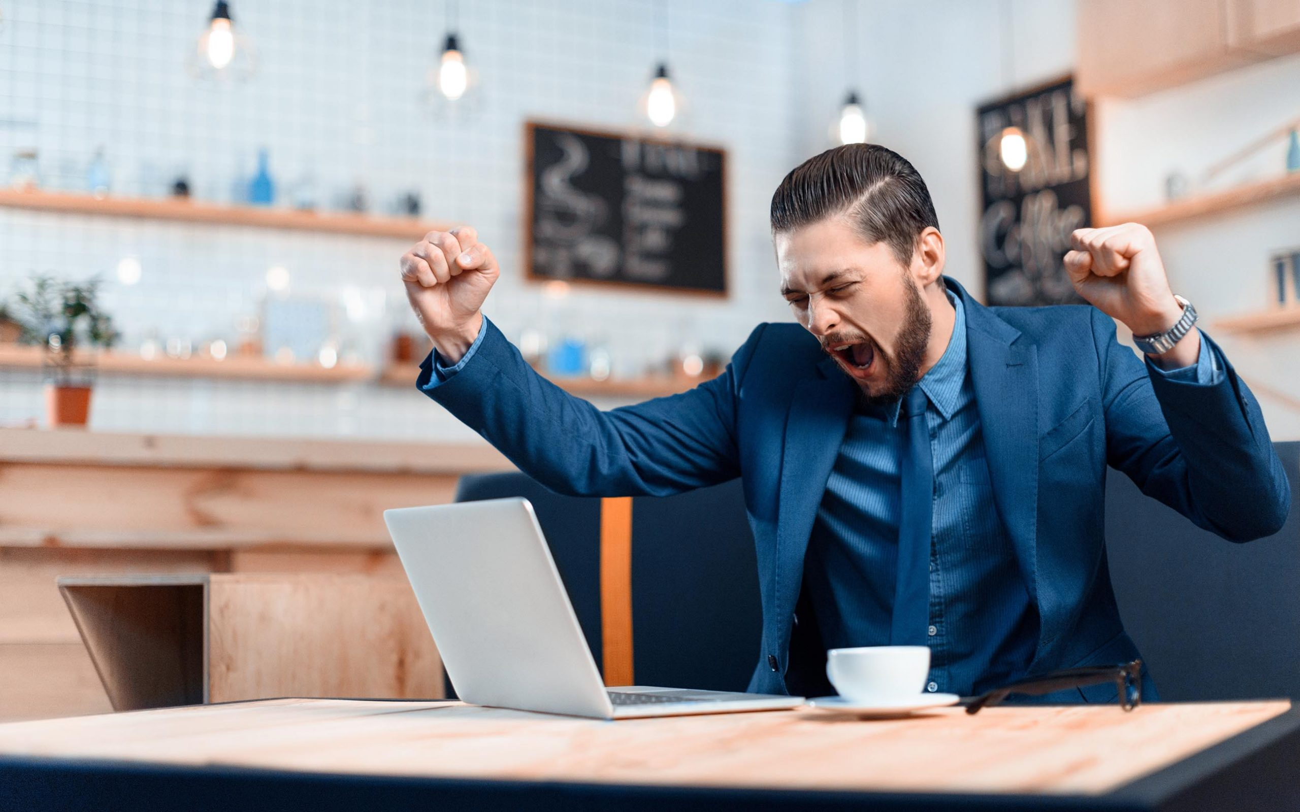 man at laptop excited about finding an email design agency